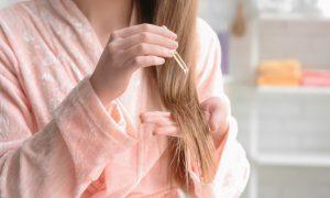 Woman applying oil onto hair