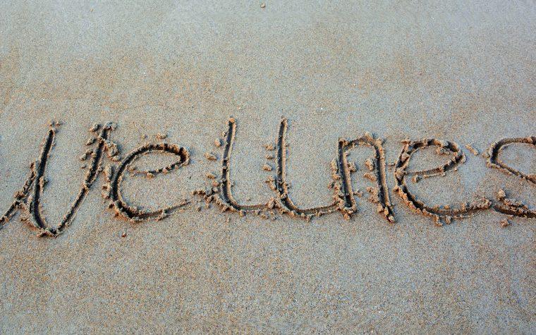 Wellness written in the sand