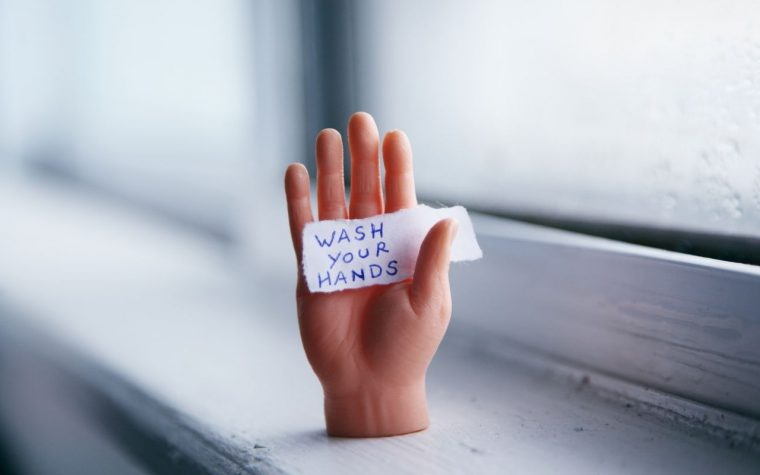 "hand holding sign saying ""wash your hands"""