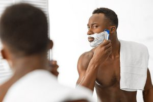 Man shaving face in mirror