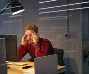 man at desk with headache