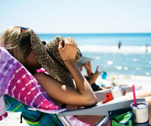 woman sunbathing on a chair with hat covering her face